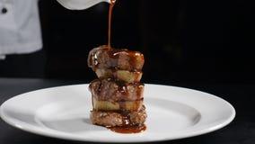 Vídeo do alimento no movimento lento Molho de derramamento do cozinheiro chefe no bife franzido Serviço do prato da carne do rest video estoque