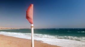 vídeo do close up 4k da bandeira vermelha que vibra na praia no dia ventoso video estoque