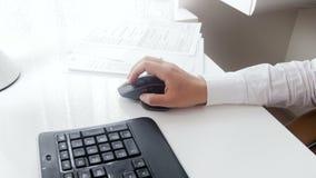 Vídeo do close up 4k da mão fêmea usando o rato preto do computador no escritório video estoque