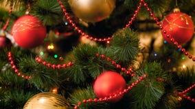 Vídeo do close up 4k de luzes coloridas e das quinquilharias que penduram na árvore de Natal na sala de visitas Metragem perfeita filme