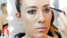 vídeo do close up 4k do maquilhador profissional que aplica o rímel e que pinta olhos e as testas dos modelos no profissional vídeos de arquivo
