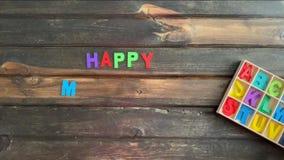 Vídeo do lapso de tempo aéreo da mão de uma criança que soletra para fora a mensagem feliz do dia de mães em letras de bloco colo vídeos de arquivo
