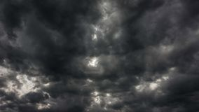 Vídeo do lapso de tempo das nuvens pretas tormentosos que passam atrás do sol vídeos de arquivo