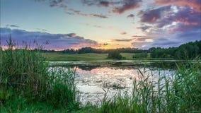Vídeo do lapso de tempo do lago e da passagem colorida das nuvens vídeos de arquivo