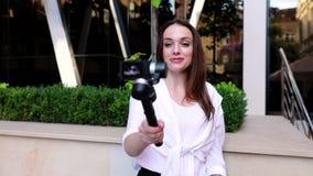 Vídeo do película da mulher na câmera perto do prédio de escritórios moderno filme