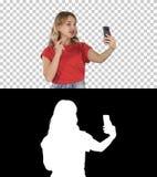 Vídeo fêmea alegre da gravação do blogger à câmera dianteira do telefone moderno ao andar, Alpha Channel imagem de stock royalty free