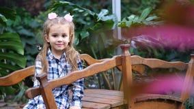 Vídeo fabuloso Una muchacha encantadora se está sentando en el puente, una mariposa está volando en su hombro 4K MES lento almacen de video