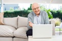 Vídeo feliz del hombre mayor que charla en el ordenador portátil en el pórtico fotografía de archivo