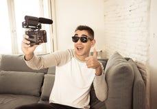 Vídeo feliz novo da gravação do blogger na câmera para o polegar da exibição do blogue do Internet acima foto de stock
