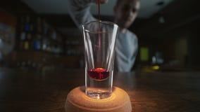 Vídeo granangular del marco de verter el licor rojo al vidrio en el alcohol a cámara lenta, de colada en una barra, camarero en almacen de metraje de vídeo