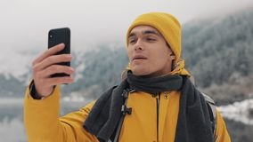 Vídeo hermoso del hombre del caminante que invita a smartphone, agitando en la cámara, sonriendo y hablando con los amigos Invier almacen de metraje de vídeo