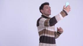 Vídeo hispánico feliz joven del hombre que llama y que muestra el teléfono listo para el invierno almacen de metraje de vídeo