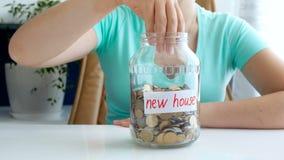vídeo 4k conceptual do dinheiro de coleta e de salvamento da jovem mulher para a casa nova Pouco appeairng da casa do brinquedo n vídeos de arquivo