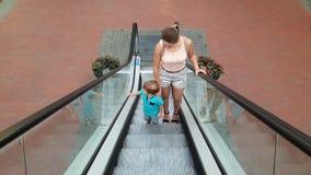 vídeo 4k da mãe nova bonita com equitação do filho da criança na escada rolante no shopping Terra arrendada do menino por trilhos filme