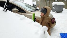 vídeo 4k de 3 años del niño pequeño que ayuda limpiando el coche cubierto en nieve después de nevada almacen de video