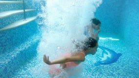 vídeo 4k de dois adolescentes que guardam as mãos e que saltam na piscina Vista de debaixo da ?gua Jogo de Childs filme