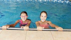 vídeo 4k de dos adolescentes sonrientes que miran in camera y que se zambullen en piscina metrajes