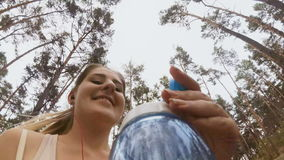vídeo 4K de la cámara atada a la botella de mujer sonriente joven que corre en el parque almacen de metraje de vídeo