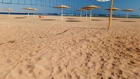 vídeo 4k de la cámara que se mueve desde bola hacia la red del voleibol en la playa del mar metrajes