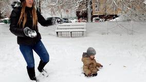 vídeo 4k de la madre joven que juega con su hijo del niño en parque del invierno y bolas de nieve que lanzan almacen de metraje de vídeo