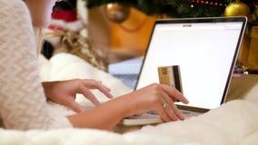 vídeo 4k de la mujer joven que hace las compras en línea para la Navidad Ella está sosteniendo la tarjeta de crédito y está utili metrajes