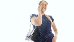 vídeo 4k de la mujer sonriente hermosa que habla por el teléfono contra el fondo blanco almacen de metraje de vídeo