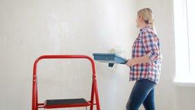 vídeo 4k de la paleta de la tenencia de la mujer joven y de paredes de pintura en su casa bajo renovación con el rodillo de pintu