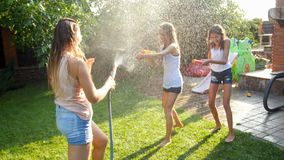 vídeo 4k de rir a família feliz que joga com mangueira de jardim e armas de água no quintal da casa video estoque