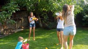 vídeo 4k de rir a família feliz que tem a batalha da água na grama no quintal video estoque