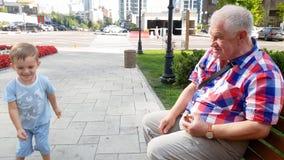 vídeo 4k del abuelo con el helicóptero de lanzamiento del juguete del nieto en banco en el parque metrajes