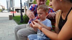 vídeo 4k del helicóptero de lanzamiento joven del juguete de la madre, del abuelo y del niño pequeño en banco en el parque almacen de metraje de vídeo