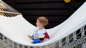 vídeo 4k del niño pequeño feliz sonriente que se sienta en hamaca en el patio trasero almacen de metraje de vídeo