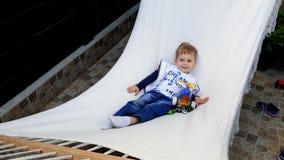 vídeo 4k del niño pequeño sonriente que miente y que balancea en hamaca Cild que se relaja en el patio trasero de la casa almacen de metraje de vídeo