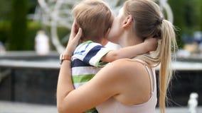 vídeo 4k del pequeño niño pequeño trastornado que llora y que abraza su mothe en el parque almacen de metraje de vídeo