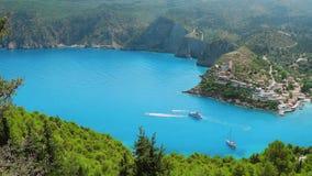 vídeo 4k del pueblo turístico popular de Assos del lugar en la isla de Kefalonia Rodeado por el verdor enorme, agua azul clara metrajes