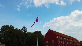 vídeo 4K do dinamarquês da bandeira de Dinamarca que funde no céu azul É situado no centro de Copenhaga filme