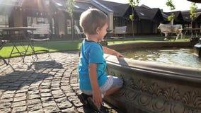 vídeo 4k do menino adorável da criança que toca na água na fonte no parque video estoque