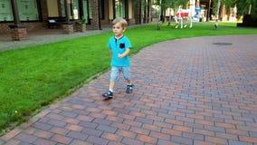 vídeo 4k do menino de sorriso da criança que corre no parque bonito do verão video estoque