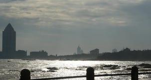 vídeo 4k, edificio y olas oceánicas urbanos, costa de la playa de la puesta del sol almacen de metraje de vídeo