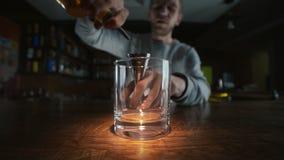 Vídeo macro granangular del whisky de colada al vidrio en el alcohol a cámara lenta, de colada en una barra, camarero en el tra metrajes