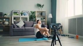 Vídeo masculino de la grabación del blogger en la cámara que habla entonces ejercitando el ABS en casa en la estera almacen de metraje de vídeo