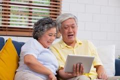 Vídeo mayor asiático feliz de la tableta del uso de los pares que charla a la familia en casa envejecimiento en casa de concepto fotos de archivo