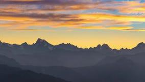 Vídeo panorâmico nos cumes no por do sol Céu colorido, picos de montanha da alta altitude com geleiras, parque nacional do DES Ec vídeos de arquivo