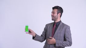 Vídeo persa barbudo feliz del hombre de negocios que llama y que muestra el teléfono almacen de metraje de vídeo