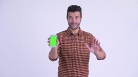 Vídeo persa barbudo feliz del hombre del inconformista que llama y que muestra el teléfono metrajes