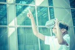 Vídeo que juega o de observación del niño con los vidrios de la realidad virtual en la ciudad Imagen de archivo