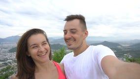 Vídeo sonriente feliz de la grabación de los pares, tomando el selfie en las montañas con la opinión aérea de la ciudad El hombre metrajes