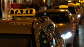 Vídeo suave de mano de la noche del foco de taxis y de la gente en Berlín, Alemania