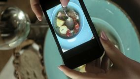 Vídeo vertical Vídeo vertical Alimento das fotografias da mulher no telefone filmando o alimento filme