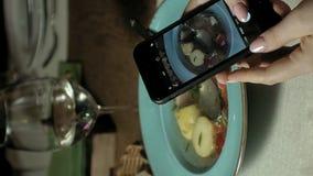 Vídeo vertical Vídeo vertical Alimento das fotografias da mulher no telefone filmando o alimento video estoque